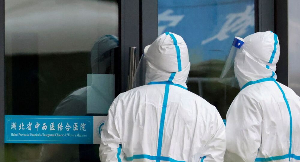 Staff members in protective suits stand at Hubei Provincial Hospital of Integrated Chinese and Western Medicine where members of the World Health Organization (WHO) team tasked with investigating the origins of the coronavirus disease (COVID-19) are visiting, in Wuhan, Hubei province, China January 29, 2021.