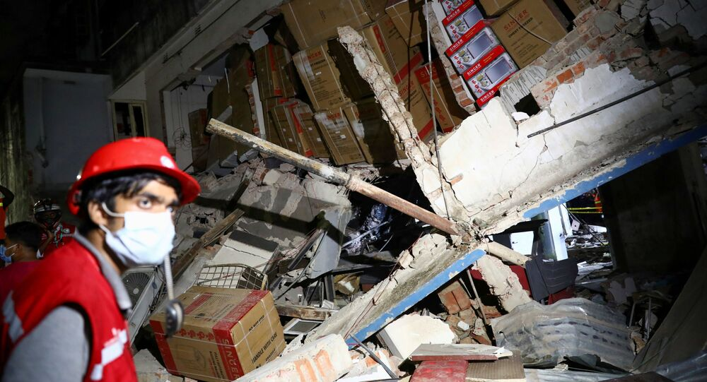 A rescue worker looks on at the site after a blast in a shop that killed several people in Dhaka, Bangladesh, June 27, 2021.