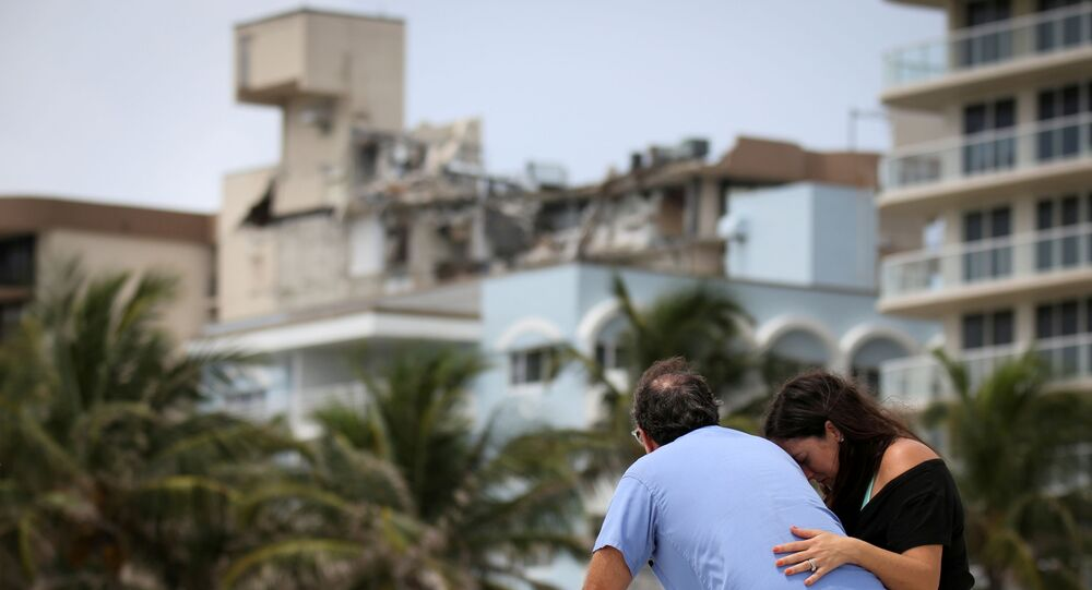 A couple at the beach reacts near the partially collapsed residential building as the emergency crews continue search and rescue operations for survivors, in Surfside, near Miami Beach, Florida, U.S. June 26, 2021.