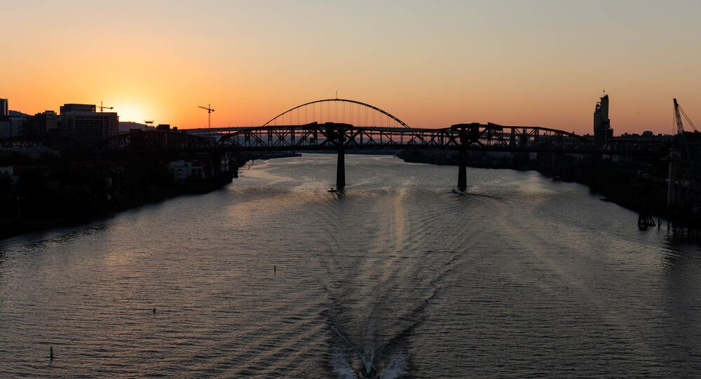 The sun sets as a boat travels down the Willamette River during a heat wave in Portland, Oregon, U.S. June 27, 2021.