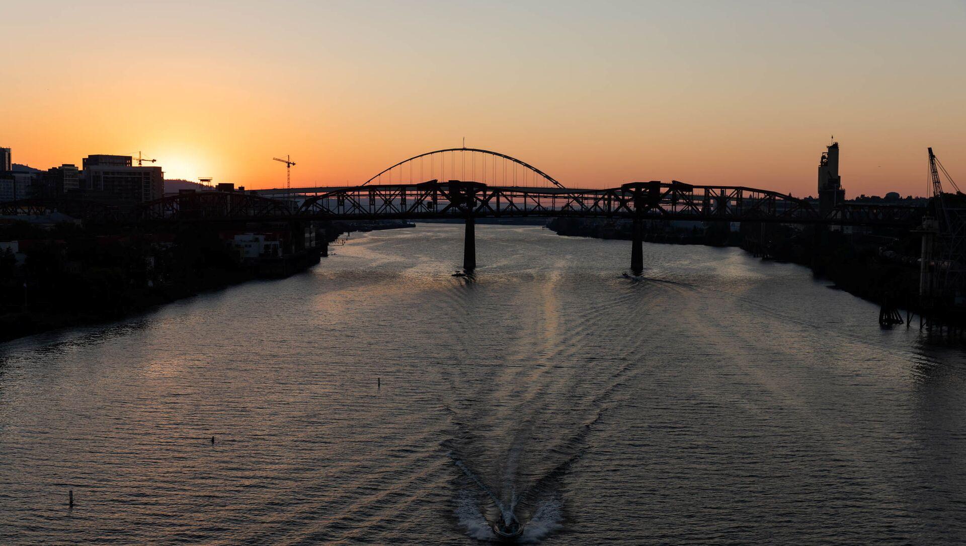 The sun sets as a boat travels down the Willamette River during a heat wave in Portland, Oregon, U.S. June 27, 2021.  - Sputnik International, 1920, 29.06.2021