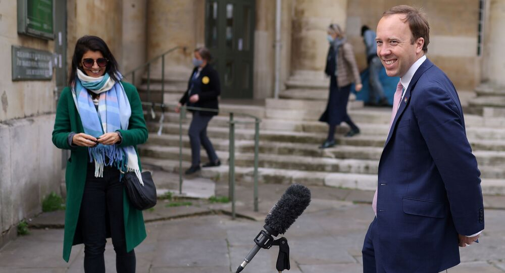 Britain's Health Secretary Matt Hancock smiles during a television interview as his aide Gina Coladangelo looks on, outside BBC's Broadcasting House in London