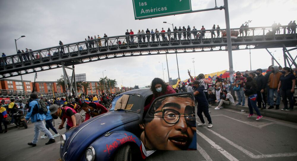 People push a car with the image of late Colombian humorist and journalist Jaime Garzon painted on it during a protest demanding government action to tackle poverty, police violence and inequalities in healthcare and education systems, in Bogota, Colombia,  June 2, 2021.