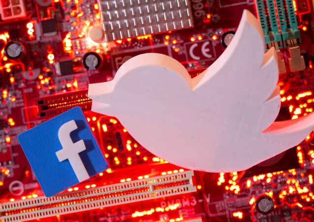 3D printed Facebook and Twitter logos are placed on a computer motherboard in this illustration taken Jan. 21, 2021
