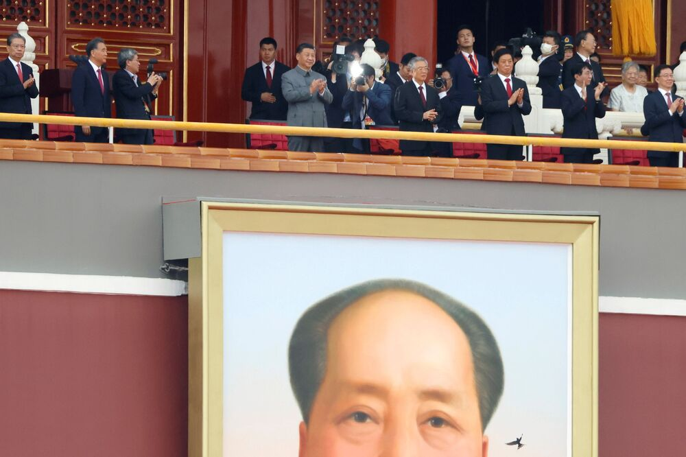 Chinese president Xi Jinping  applauding above huge portrait of chairman Mao.