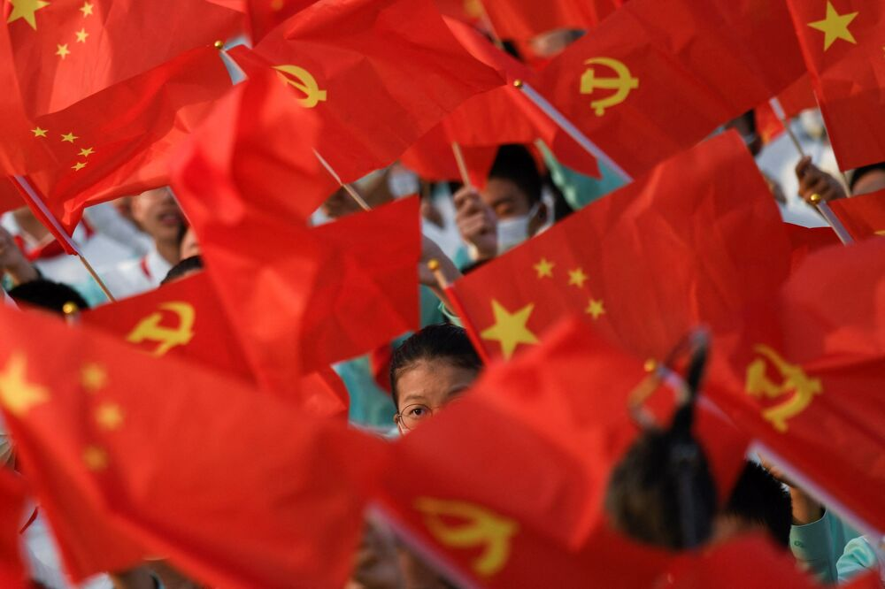 Students waiving flags during the celebration of the CCP's 100th anniversary at the Tiananmen square.