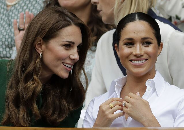In this Saturday, July 13, 2019, file photo, Kate, Duchess of Cambridge, left, and Meghan, Duchess of Sussex chat as they sit in the Royal Box on Centre Court to watch the women's singles final match between Serena Williams of the United States and Romania's Simona Halep on day twelve of the Wimbledon Tennis Championships in London