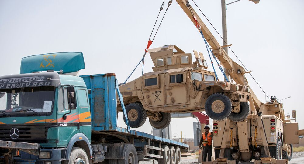 U.S. Army soldiers and contractors load High Mobility Multi-purposed Wheeled Vehicles, HUMVs, to be sent for transport as U.S. forces prepare for withdrawl, in Kandahar, Afghanistan, July 13, 2020.