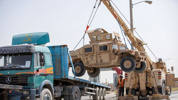 U.S. Army soldiers and contractors load High Mobility Multi-purposed Wheeled Vehicles, HUMVs, to be sent for transport as U.S. forces prepare for withdrawl, in Kandahar, Afghanistan, July 13, 2020. - Sputnik International