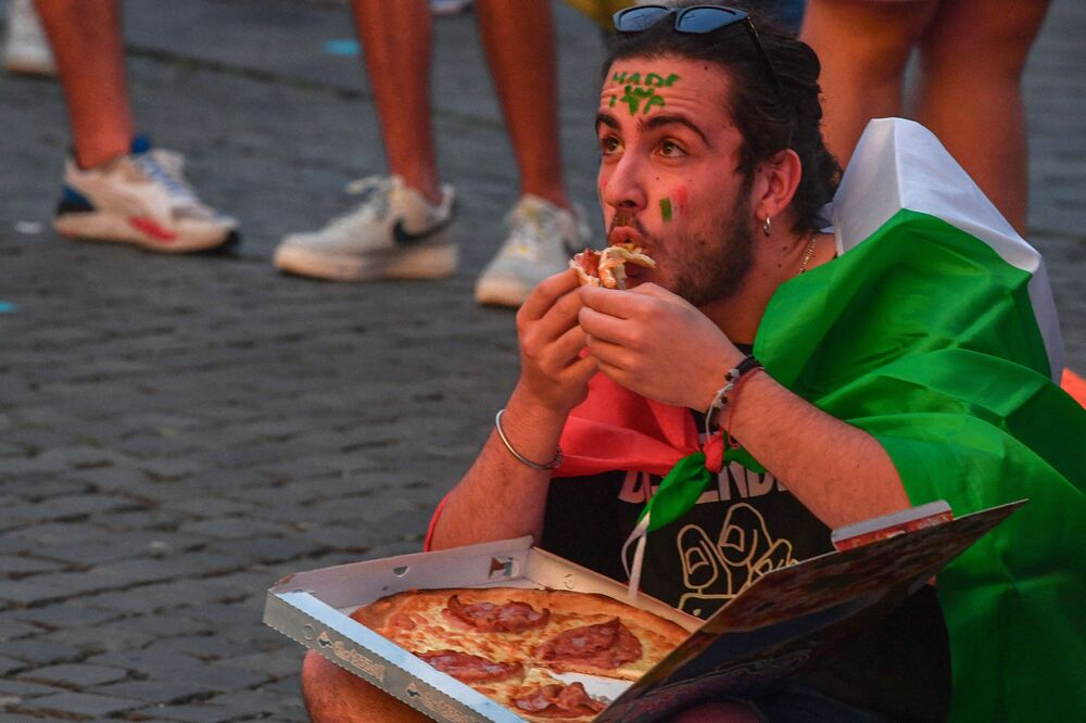 A fan of Italy eats pizza at the fan zone on Piazza del Popolo in Rome on 16 June 2021 while watching the UEFA EURO 2020 Group A football match on giant screens between Italy and Switzerland, played at the nearby Olympic Stadium.