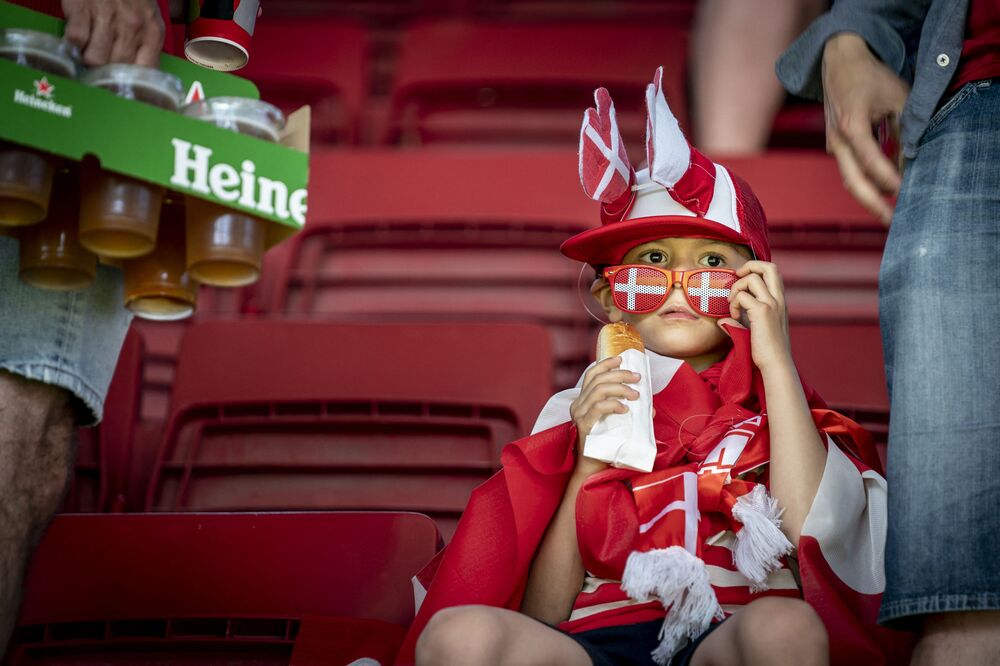 A young Denmark fan with a hot dog waits for the start of the UEFA EURO 2020 Group B football match between Denmark and Belgium at Parken Stadium in Copenhagen on 17 June 2021.