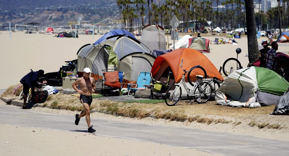 In this 8 June 2021, file photo, a jogger walks past a homeless encampment in the Venice Beach section of Los Angeles