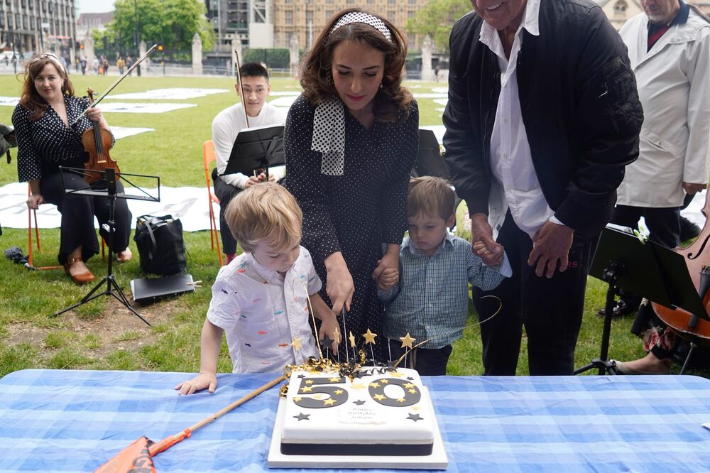 Stella Moris with their children cuts a birthday cake during a picnic in Parliament Square with her children.