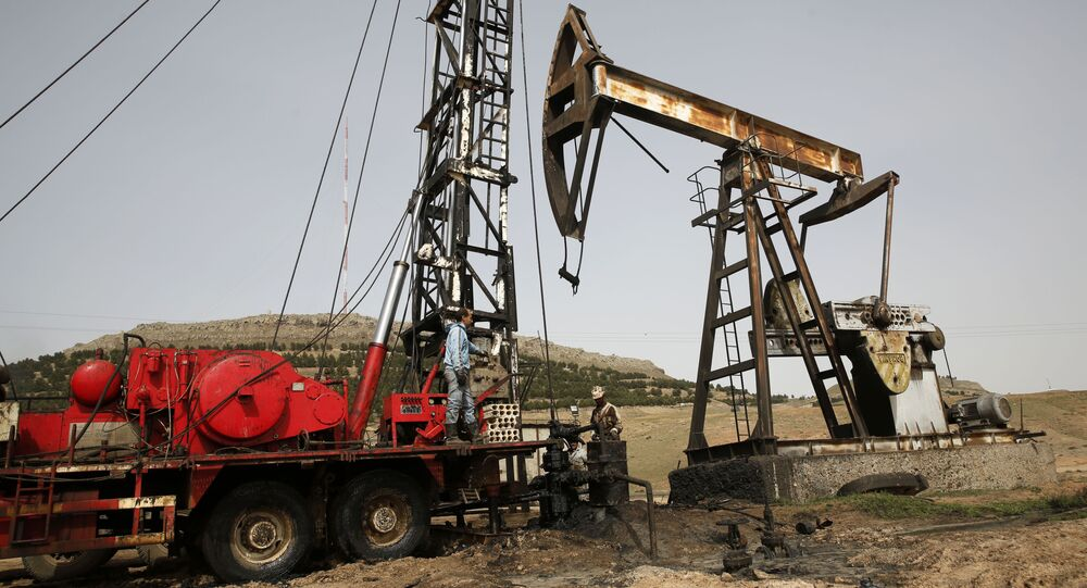 This March 27, 2018 file photo shows Syrian workers fixing pipes of an oil well at an oil field controlled by a U.S-backed Kurdish group, in Rmeilan, Hassakeh province, Syria.