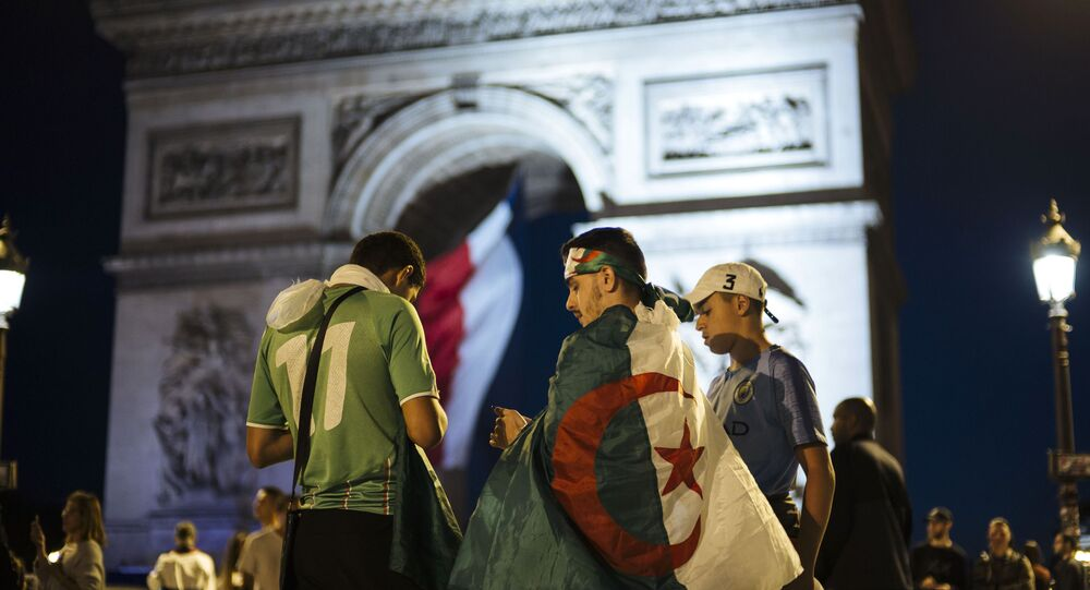 Algerians fans check their phones as the Arc de Triomphe is seen in the background after the African Cup of Nations semifinal soccer match between Algeria and Nigeria in Paris, France, Sunday, July 14, 2019.