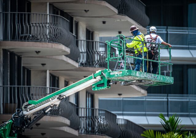 Rescuers and firefighters inspect the balconies of the partially collapsed 12-story Champlain Towers South condominium building on July 4, 2021 in Surfside, Florida. - Searchers recovered two more bodies to bring the death toll in the Florida apartment block collapse to 24, authorities said July 3, 2021, as the search for victims paused in the afternoon so demolition crews could prepare to bring down the part of the building still standing.The razing took on special urgency as Tropical Storm Elsa churned in the Caribbean, following a path expected to bring it to Florida early next week.