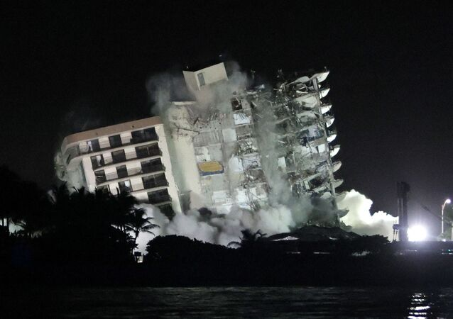 The remaining part of the partially collapsed 12-story Champlain Towers South condo building falls with a controlled demolition on July 4, 2021 in Surfside, Florida. The decision by officials to bring the rest of the building down was brought on by the approach of Tropical Storm Elsa and fears that the structure might come down in an uncontrolled fashion. Over one hundred people are missing as the search-and-rescue effort continues.