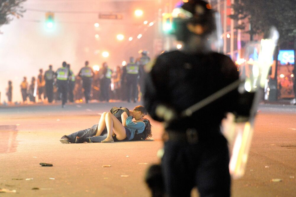 Riot police walk in the street as a couple kiss on 15 June 2011 in Vancouver, Canada.