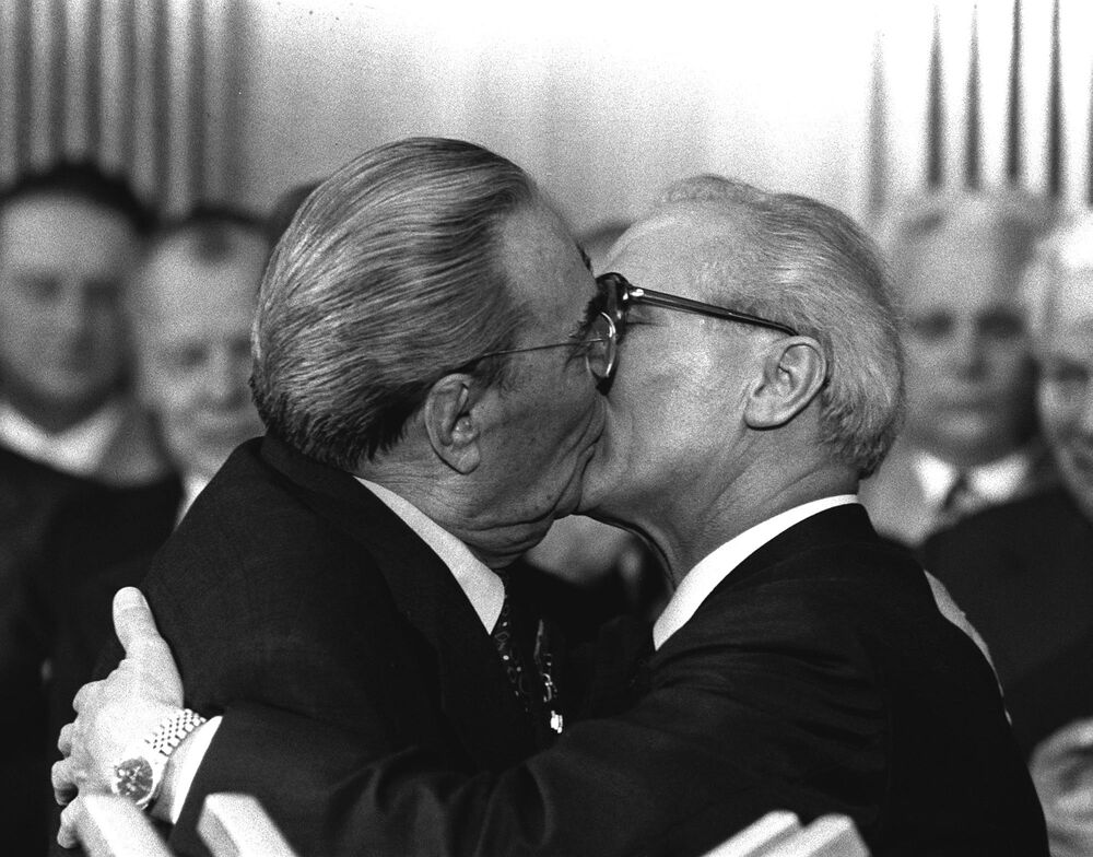 Soviet General Secretary Leonid Brezhnev and East German leader Erich Honecker exchange kisses after Brezhnev was honoured with the title Hero of the German Democratic Republic and the Karl Marx Medal, 1979.