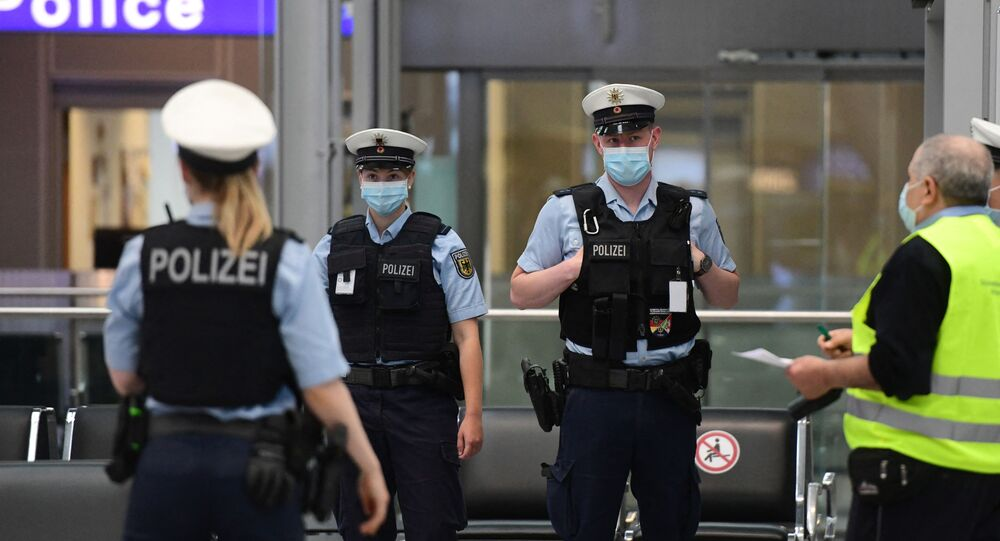 Police officers wearing face masks stand at the Duesseldorf airport, western Germany, on June 15, 2020