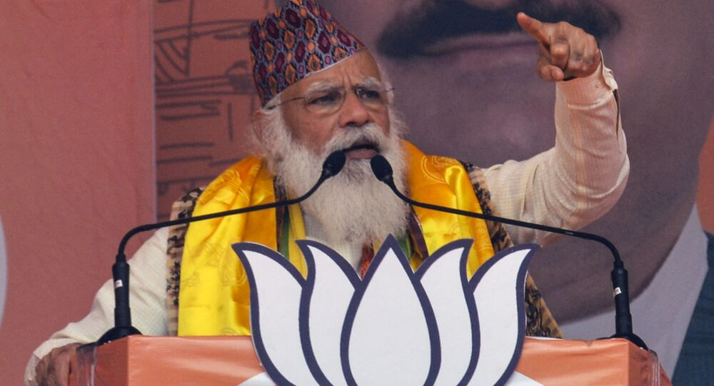 Indian Prime Minister Narendra Modi gestures as he speaks in a rally during the ongoing Phase 4 of West Bengal's assembly election, at Kawakhali on the outskirts of Siliguri on April 10, 2021