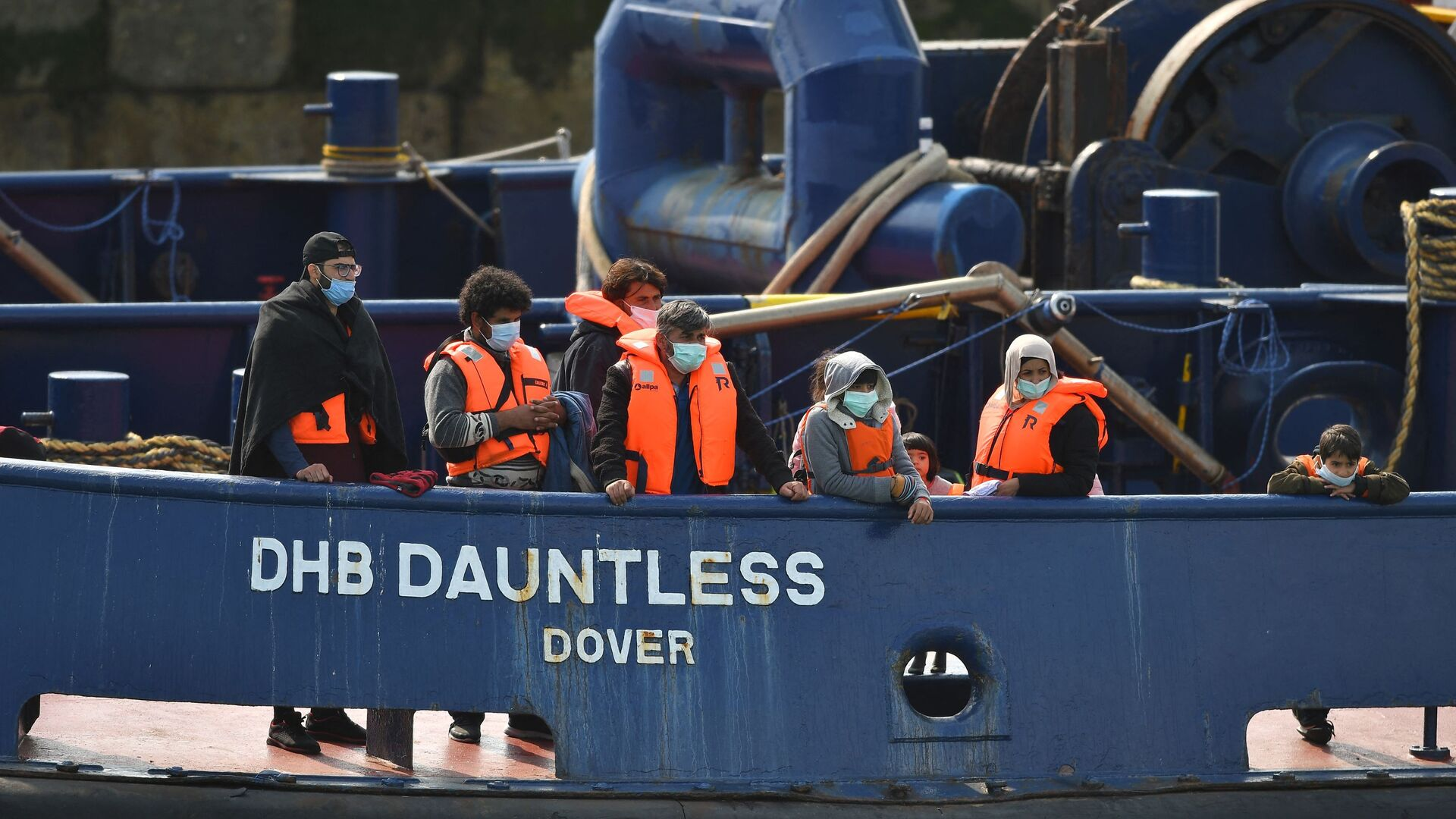Waleed (3L), 29, a Kuwaiti migrant, stands with other migrants onboard the DHB Dauntless tug boat as they are brought to shore by the UK Border Force after illegally crossing the English Channel from France on a dinghy on September 11, 2020, in the marina at Dover, on the south coast of England - Sputnik International, 1920, 25.07.2021
