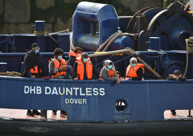 Waleed (3L), 29, a Kuwaiti migrant, stands with other migrants onboard the DHB Dauntless tug boat as they are brought to shore by the UK Border Force after illegally crossing the English Channel from France on a dinghy on September 11, 2020, in the marina at Dover, on the south coast of England