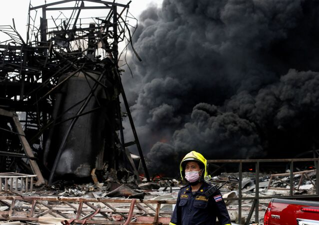 Emergency personnel looks on as smoke rises from a plastic factory after an explosion in Samut Prakan, outside Bangkok, Thailand July 5, 2021