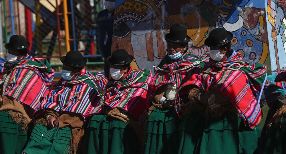 Aymara Indigenous women sit on the sidelines of a vaccination campaign against COVID-19 for people over age 50, on the border that connects  Desaguadero, Bolivia, with Desaguadero, Peru, Friday, May 21, 2021