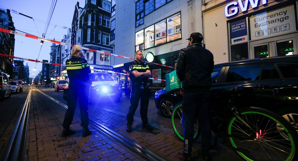 Police officers talk to a person as they stand guard in the area where Dutch celebrity crime reporter Peter R. de Vries, known for his reporting on some of the most renowned criminals in the Netherlands, was reportedly shot and seriously injured, in Amsterdam, Netherlands, July 6, 2021