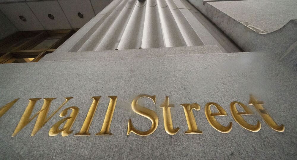 n this Nov. 5, 2020 file photo, a sign for Wall Street is carved in the side of a building. Stocks are easing lower in early trading on Wall Street, pulling major indexes slightly below the record highs they reached last week.