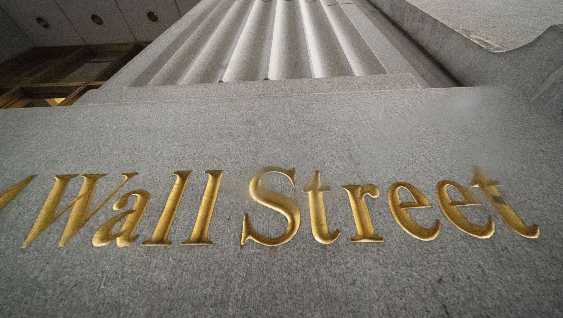 n this Nov. 5, 2020 file photo, a sign for Wall Street is carved in the side of a building. Stocks are easing lower in early trading on Wall Street, pulling major indexes slightly below the record highs they reached last week. - Sputnik International, 1920, 03.09.2021