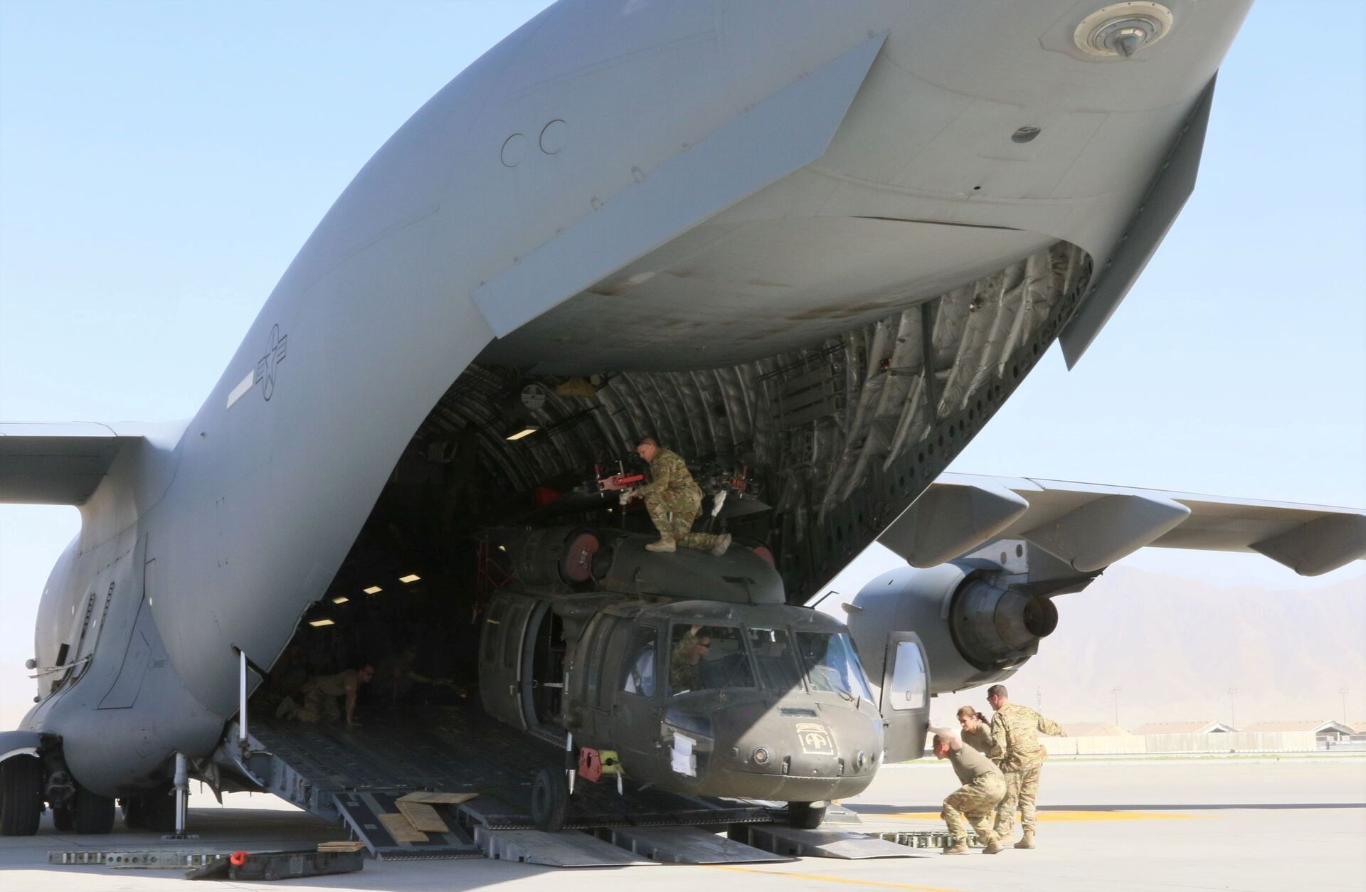 Aerial porters work with maintainers to load a UH-60L Blackhawk helicopter into a U.S. Air Force C-17 Globemaster III during the withdrawl of American forces in Afghanistan, June 16, 2021. Picture taken June 16, 2021 - Sputnik International, 1920, 07.09.2021