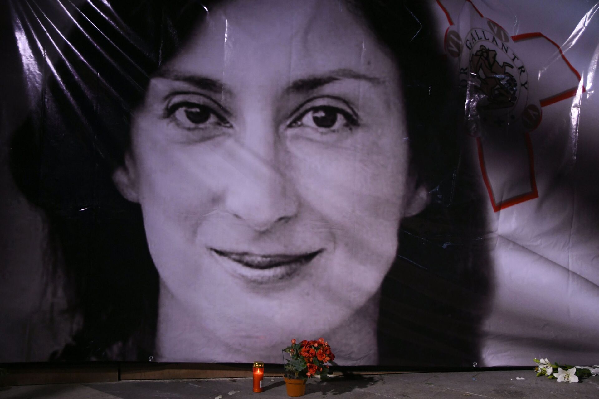 In this Tuesday, Oct. 16, 2018 file photo, flowers and a candle lie in front of a portrait of slain investigative journalist Daphne Caruana Galizia during a vigil outside the law courts in Valletta, Malta. - Sputnik International, 1920, 07.09.2021