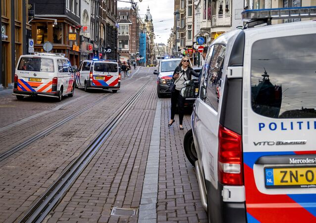 A woman walks past police vehicles parked on the site of an attack during which a Dutch journalist specialised in crime, Peter R. de Vries was seriously injured in a shooting in Amsterdam, on July 6, 2021.