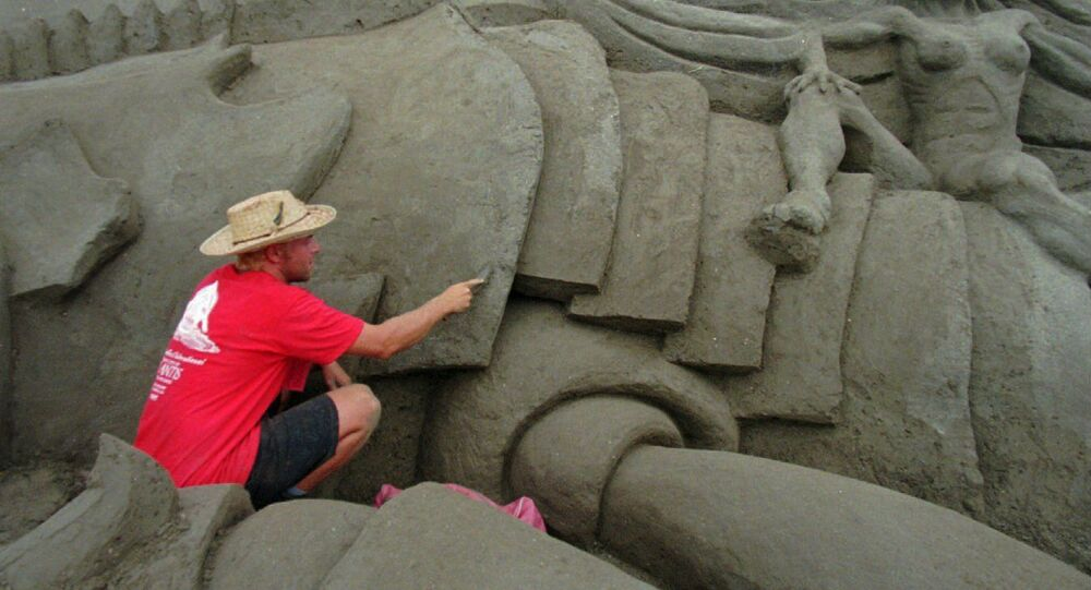 Wilfred Stijger, a sand sculptor from Holland, carves detail in a part of the The Lost City of Atlantis sand sculpture Monday Sept. 15, 1997 in San Diego