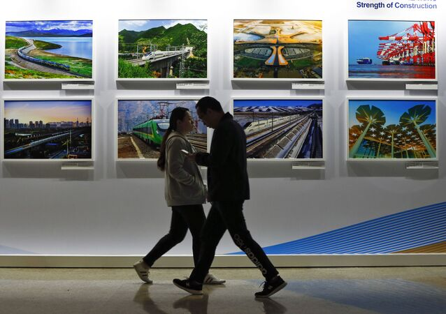 In this Saturday, April 27, 2019 file photo, people walk by a display board showcasing China's sweeping infrastructure-building projects at the media center of the Belt and Road Forum in Beijing