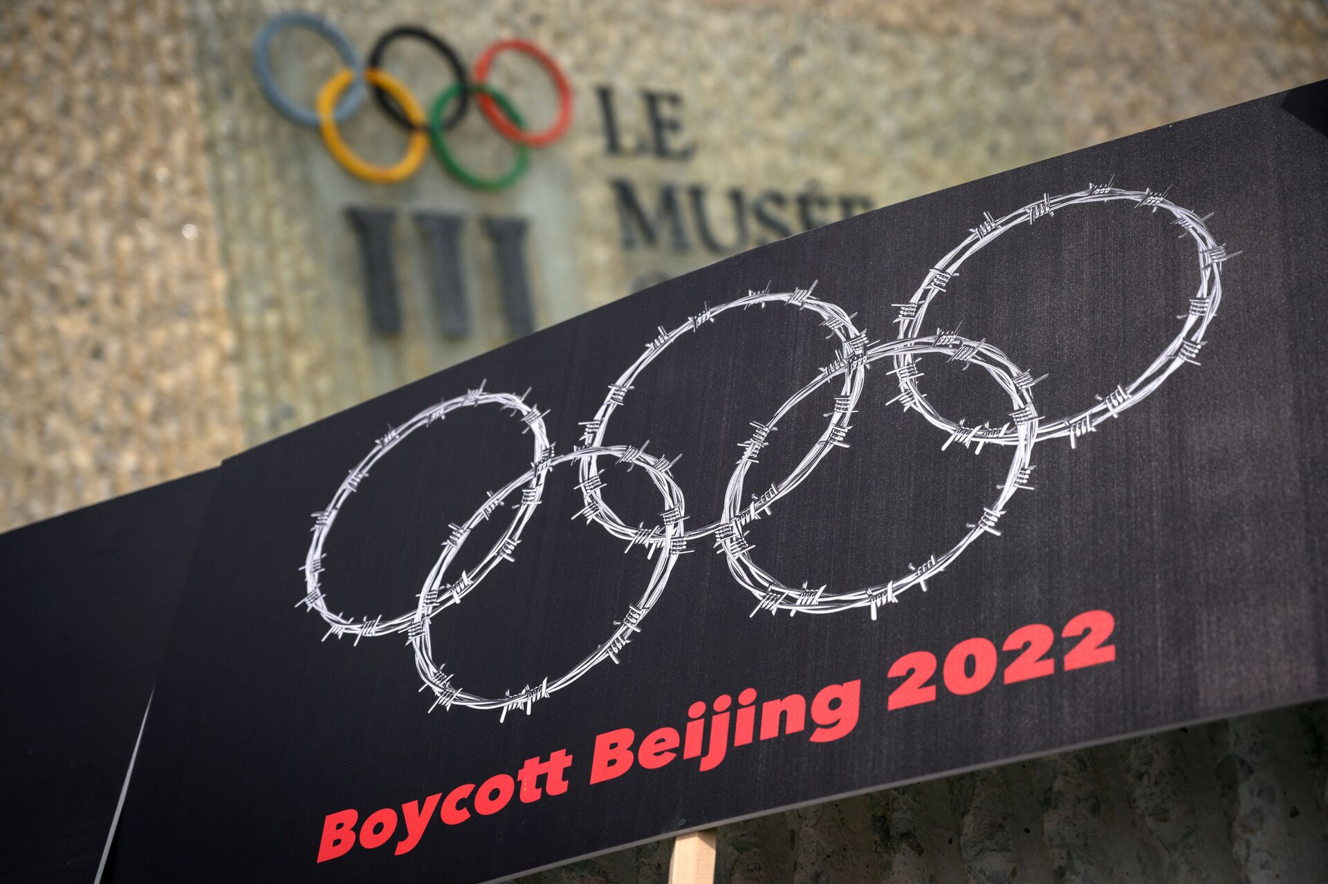 This photograph taken on June 23, 2021 shows a placard representing barber wire shaping and Olympics Rings are seen next to a sign of the Olympics Museum during a protest organised by Tibetan and Uyghur activists against Beijing 2022 Winter Olympics, in Lausanne as some 200 participants took part to the protest.  - Sputnik International, 1920, 07.09.2021