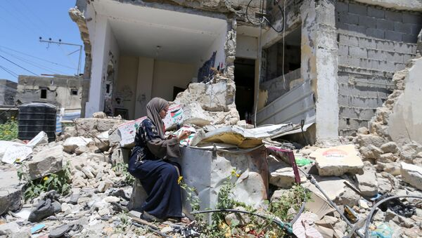 Palestinian artist Saja Mousa, 26, paints at the remains of her house that was damaged in an Israeli airstrike during last month's Israeli-Hamas fighting, in Rafah in the southern Gaza Strip June 23, 2021. Picture taken June 23, 2021. - Sputnik International
