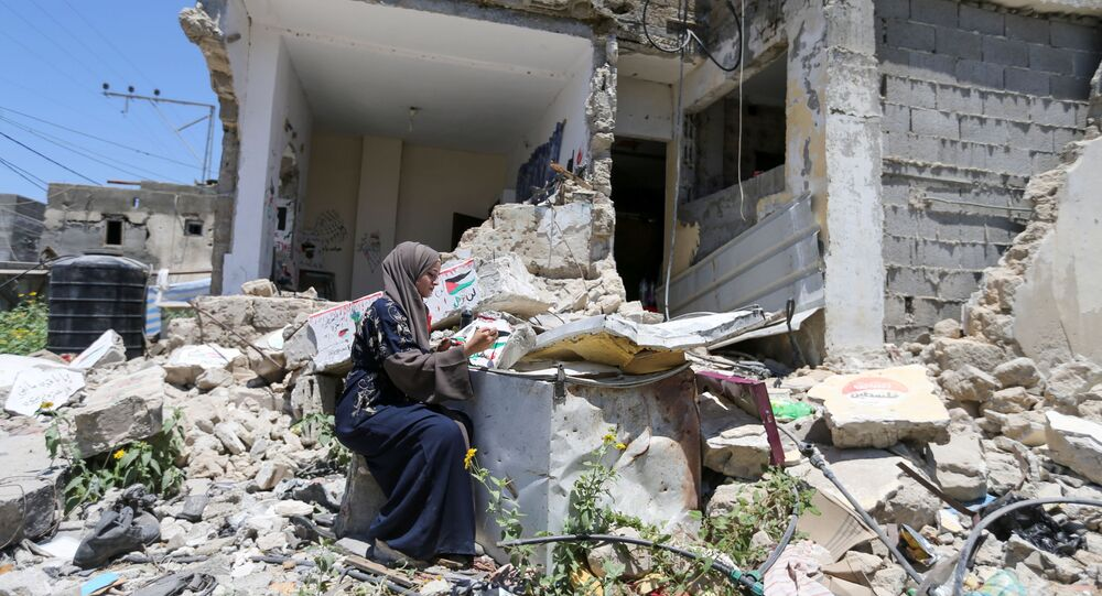 Palestinian artist Saja Mousa, 26, paints at the remains of her house that was damaged in an Israeli airstrike during last month's Israeli-Hamas fighting, in Rafah in the southern Gaza Strip June 23, 2021. Picture taken June 23, 2021.