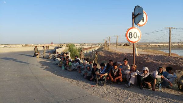 In this handout photo released by Border Troops of the State Committee for National Security of the Republic of Tajikistan on Tuesday, June 22, 2021, Afghanistan's government soldiers sit at a bridge next to Tajikistan-Afghanistan border in Tajikistan. - Sputnik International