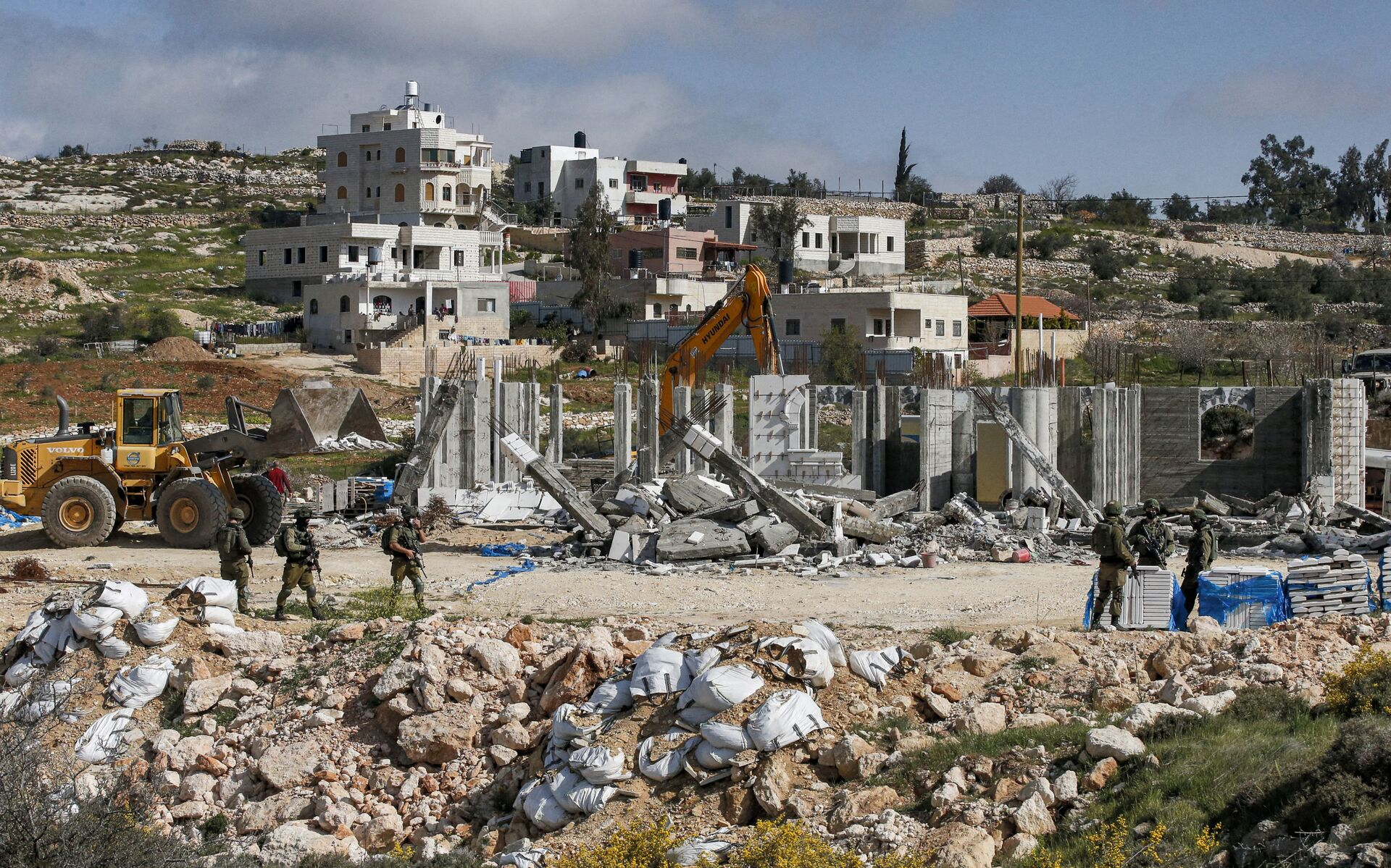 Israeli soldiers stand by as excavators demolish a Palestinian house (still under construction) located within the area C (where Israel retains full control over planning and construction) southeast of Hebron in the occupied West Bank on March 8, 2021. - Sputnik International, 1920, 07.09.2021