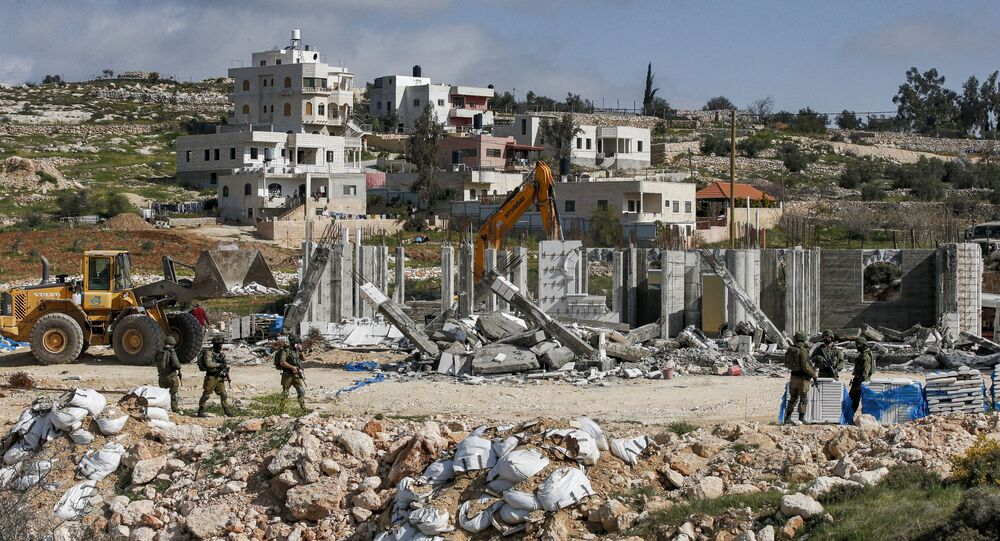 Israeli soldiers stand by as excavators demolish a Palestinian house (still under construction) located within the area C (where Israel retains full control over planning and construction) southeast of Hebron in the occupied West Bank on March 8, 2021.