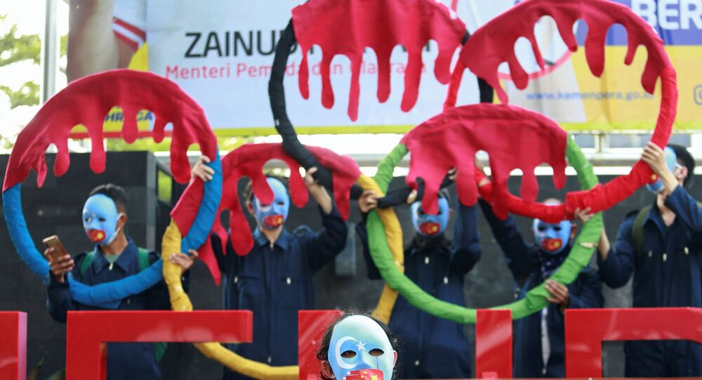 Activists wearing masks take part in a protest to boycott the Beijing 2022 Winter Olympic Games outside the Ministry of Youth and Sport of the Republic of Indonesia building in Jakarta, Indonesia, June 25, 2021