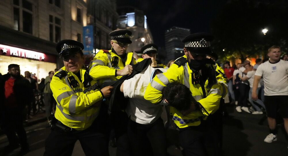 Police detain a man near Trafalgar Square during celebrations after England won the Euro 2020 soccer championship semifinal match between England and Denmark played at Wembley Stadium in London, Wednesday, July 7, 2021.