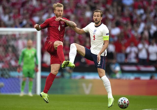 Denmark's defender Simon Kjaer (L) fights for the ball with England's forward Harry Kane during the UEFA EURO 2020 semi-final football match between England and Denmark at Wembley Stadium in London on July 7, 2021.