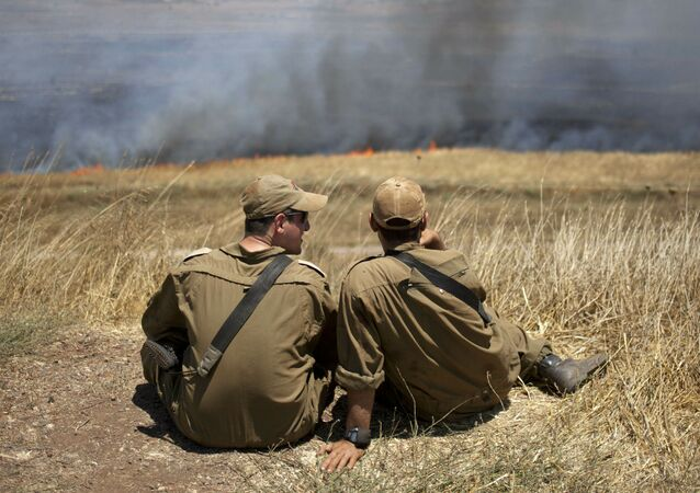 FILE - In this July 16, 2013, file photo, Israeli soldiers sit in a position on the border with Syria on the Israeli-controlled Golan Heights as smoke rises following explosions of mortar shells
