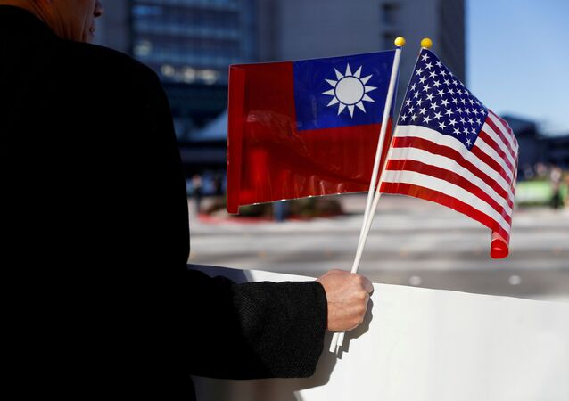 A demonstrator holds flags of Taiwan and the United States in support of Taiwanese President Tsai Ing-wen during an stop-over after her visit to Latin America in Burlingame, California, 14 January 2017. REUTERS/Stephen Lam/File Photo