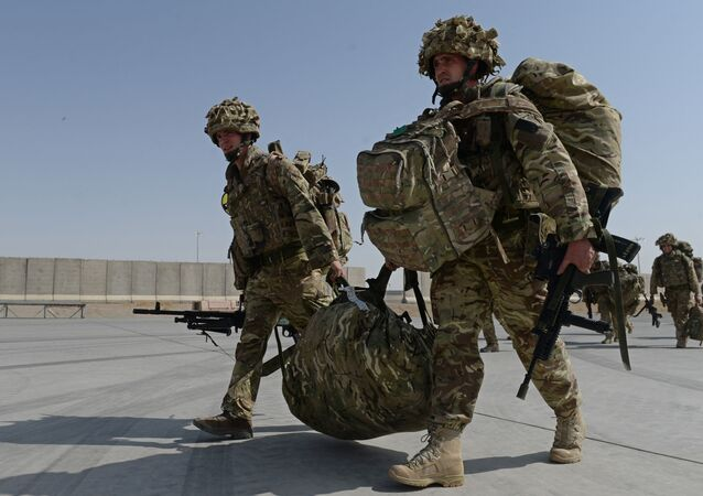 British soldiers walk with their gear after arriving in Kandahar on October 27, 2014, as British and US forces withdraw from the Camp Bastion-Leatherneck complex in Helmand province