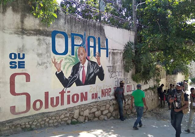 People walk past a wall with a mural depicting Haiti's President Jovenel Moise, after he was shot dead by unidentified attackers in his private residence, in Port-au-Prince, Haiti July 7, 2021.